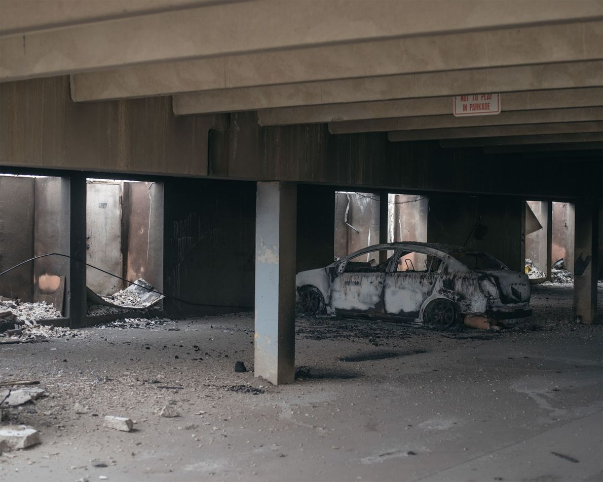An abandoned car sits in the parking garage of a burned apartment building.