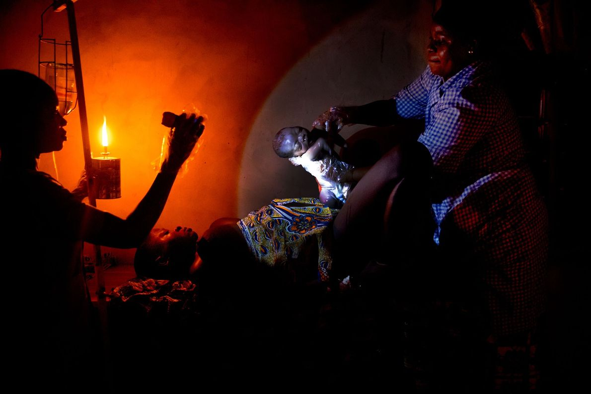 Midwife Raïssa Godjo helps deliver a baby by oil lamp torchlight in the village of Attankpe.