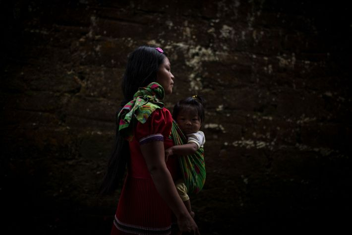 Maria, an adolescent mother, walks with her child, whose father has disappeared.