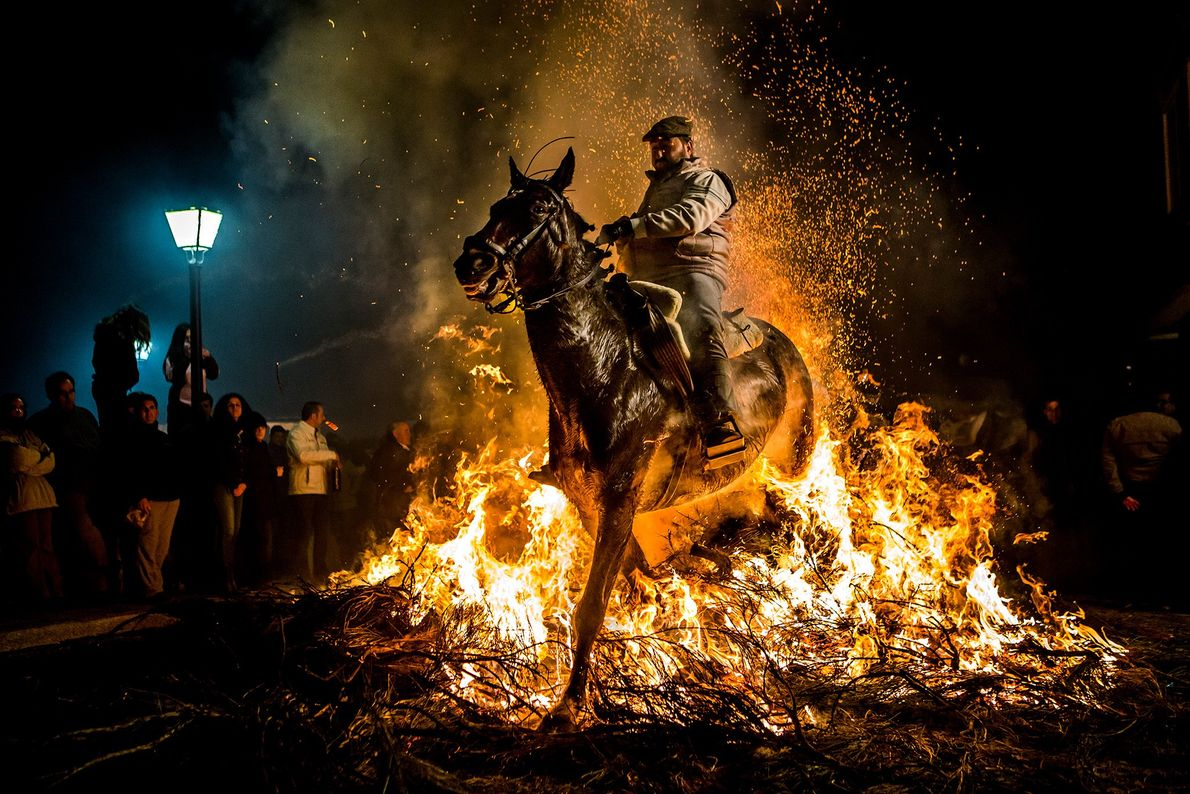Picture of a man riding a horse through flames in Spain