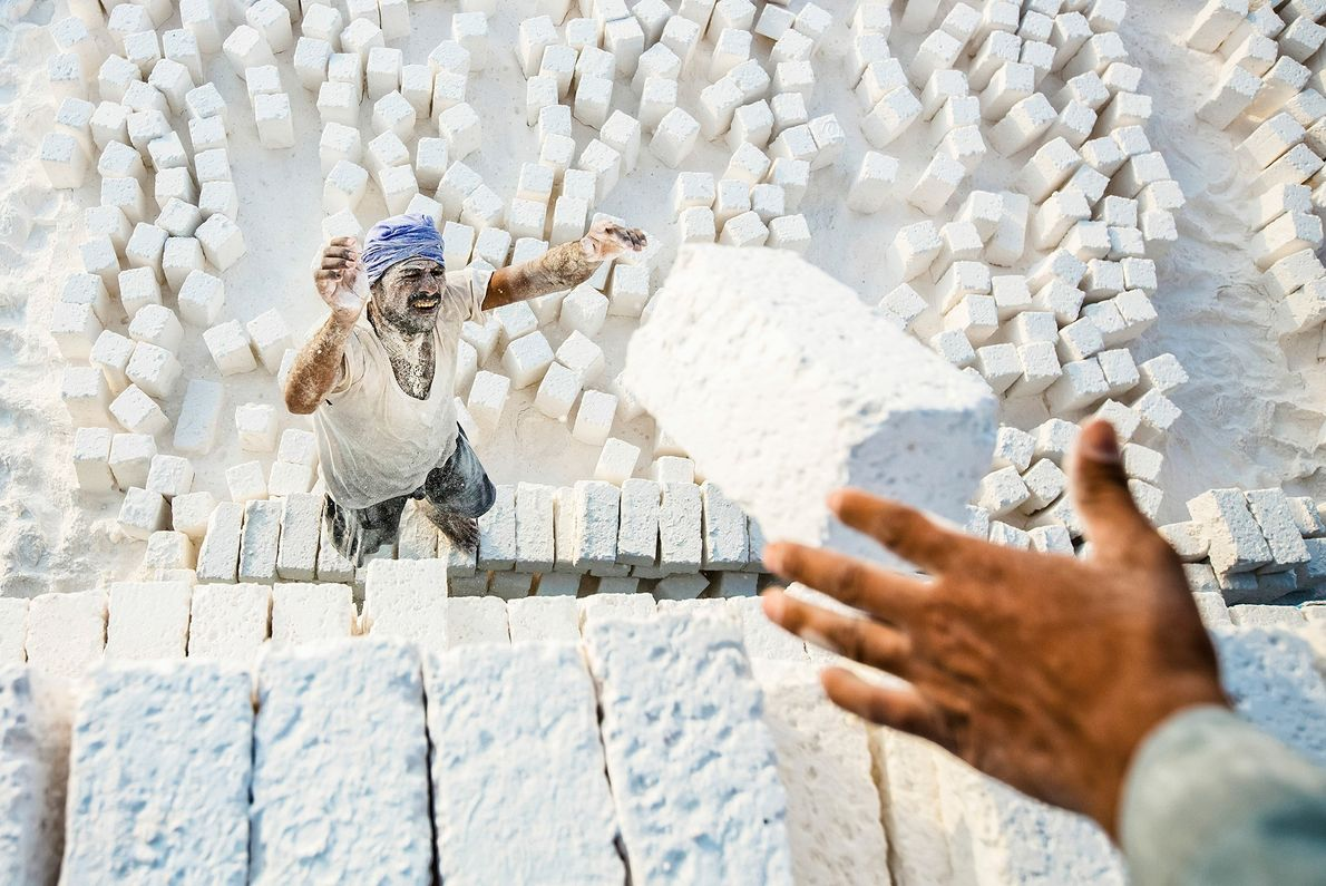 Picture of laborers loading bricks of limestone in Egypt