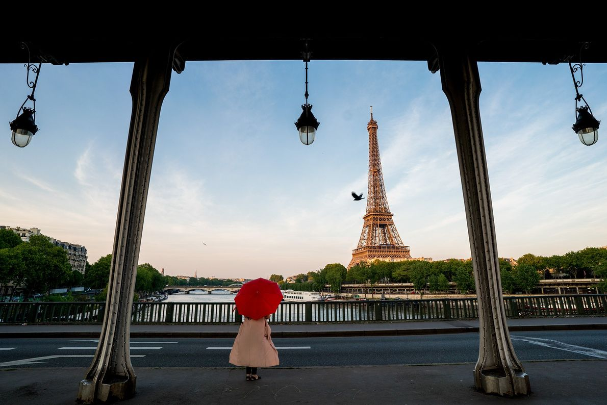 Picture of a person holding a red umbrella in front of the Eiffel Tower
