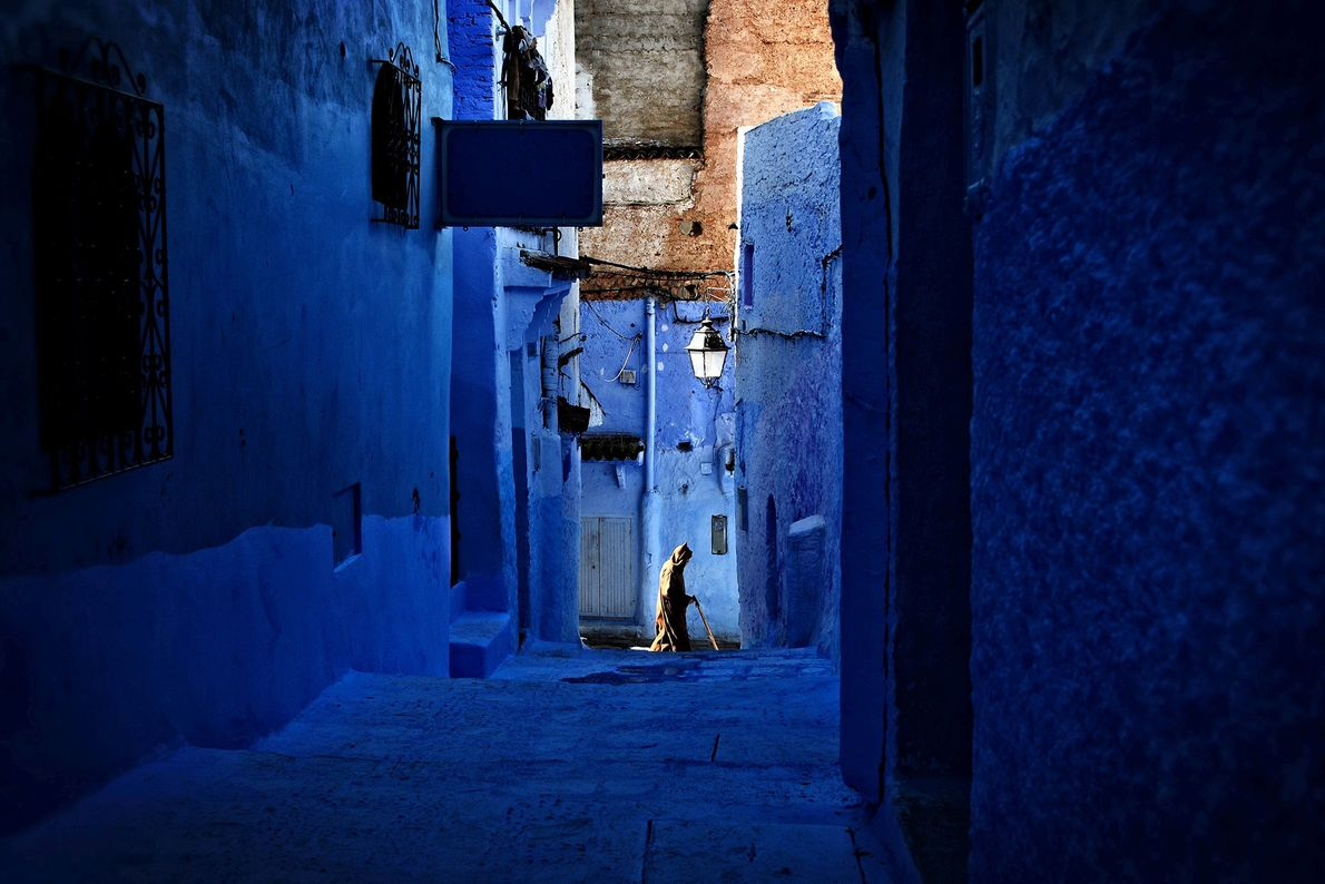 Picture of a man walking down a blue alley in Morocco