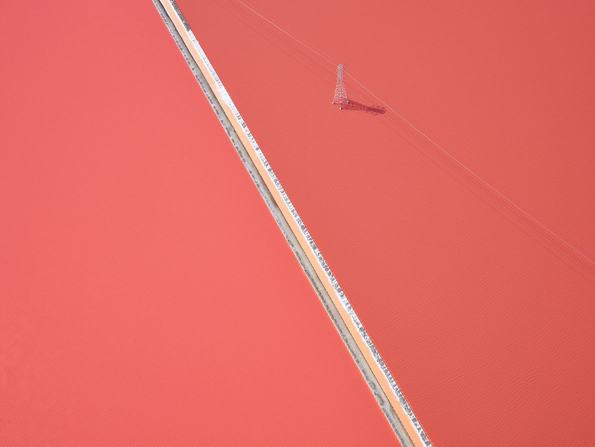 Picture of a power line stretched across pink salt flats in California