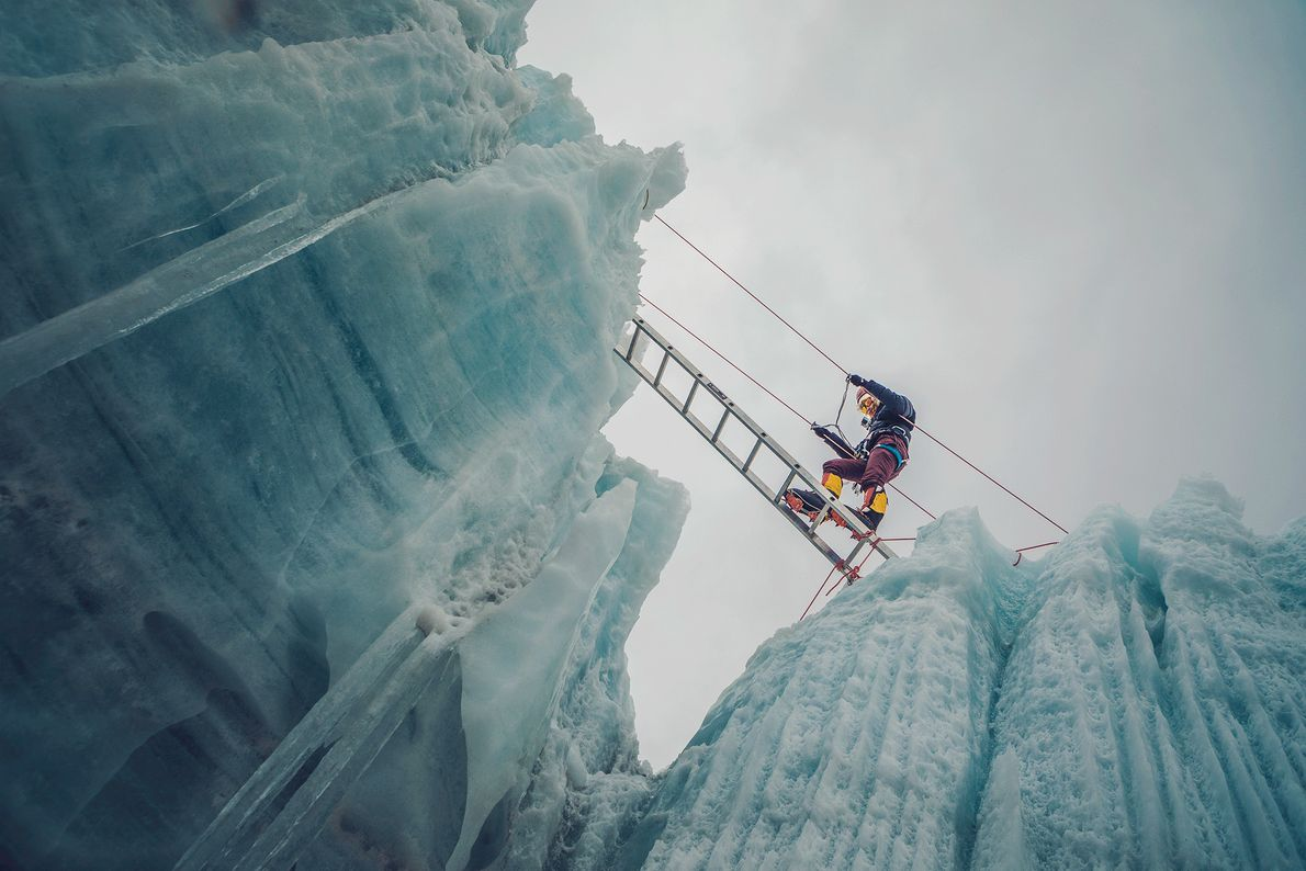 Picture of a woman crossing an icy crevasse in the Himalayas