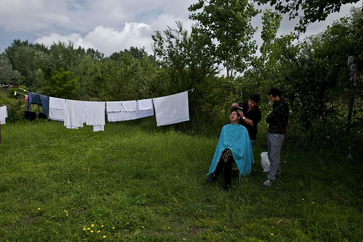 Helping each other out: A 16-year-old Afghan gets a haircut from another refugee while his teenage ...