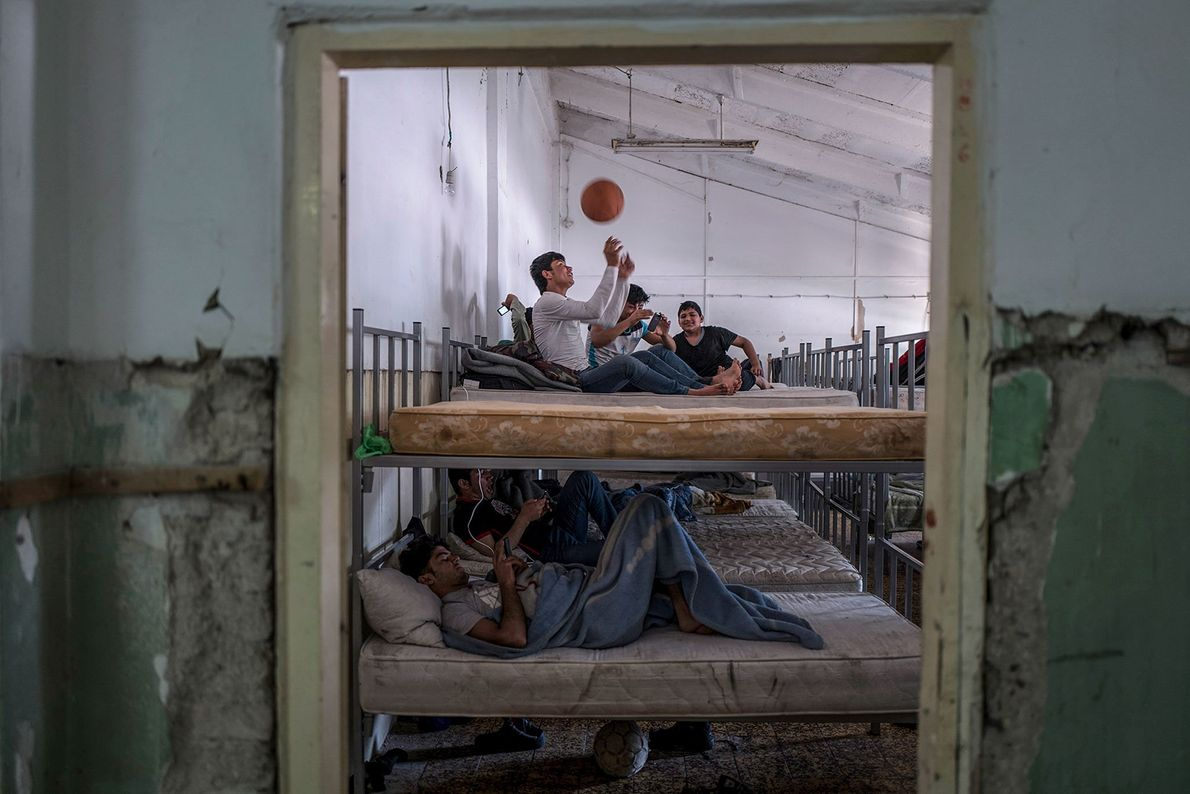 Boys play with a basketball and look at their phones inside the Obrenovac refugee center, formerly ...