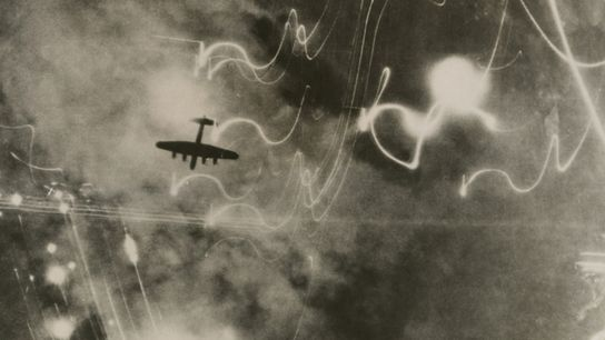British RAF bomber and trails of light from incendiary bombs. Photo taken of the bombing of ...