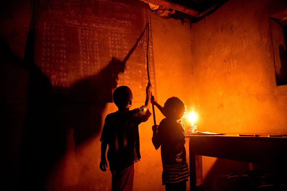 Each evening, Rogathien and Eveline Honon do their homework by light of kerosene lanterns at home ...