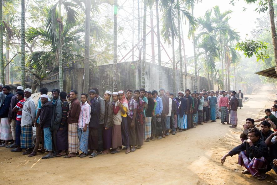 Rohingya refugees queue outside Kutupalong camp near the town of Cox's Bazar, waiting to receive staples ...