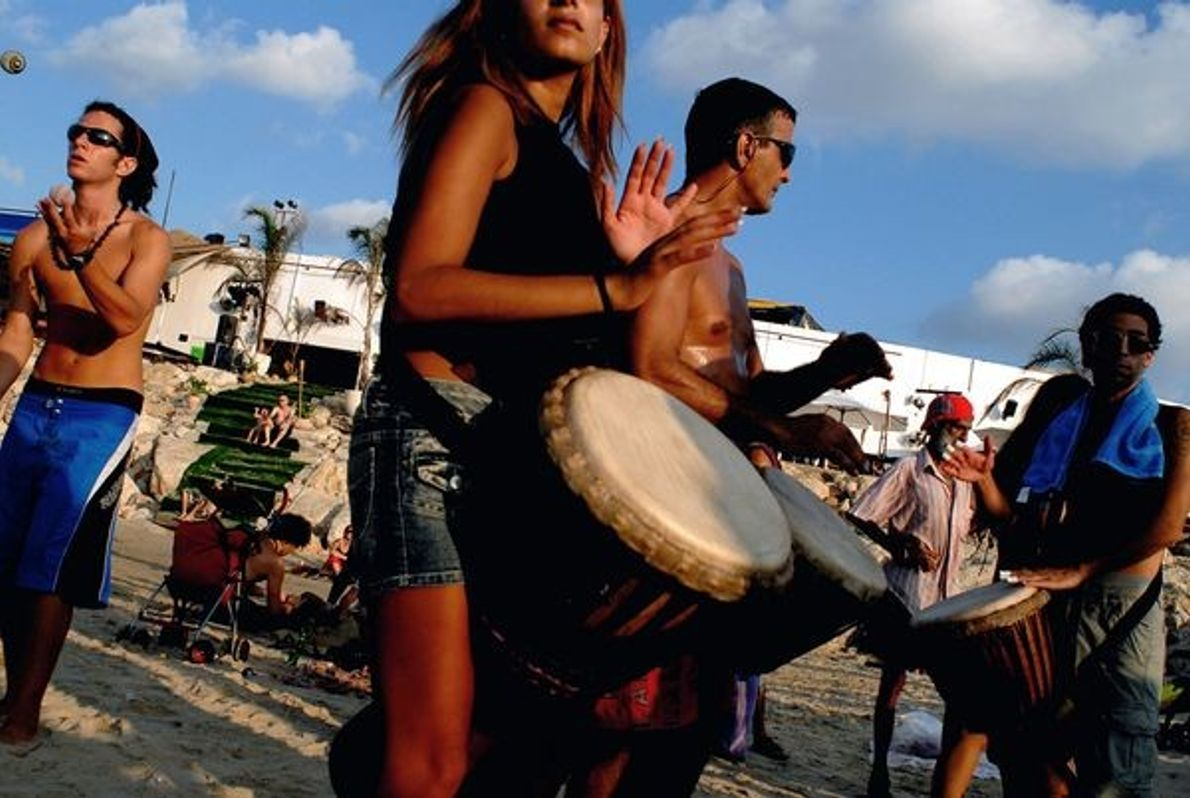 Photo: Woman and man play drums on the beach