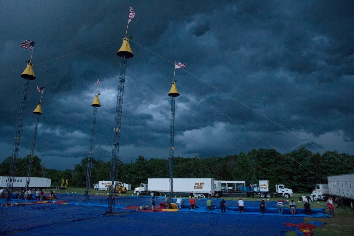 Workers from the Cole Bros. Circus rush to take down the big top as a storm ...