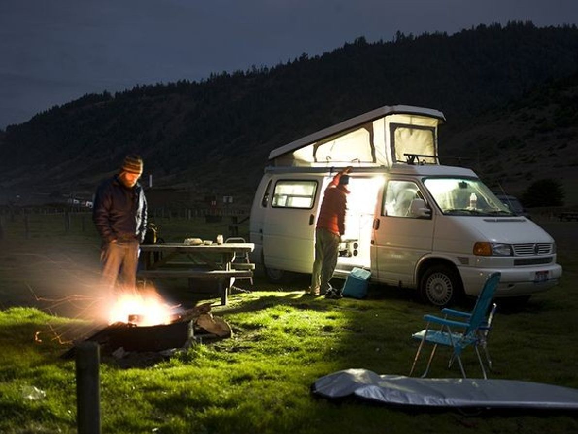 Picture of people camping from their van.